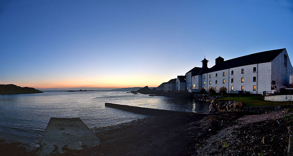 Panoramic picture of a bay with a distillery at sunset
