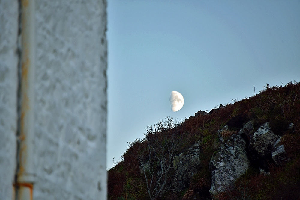Picture of the Moon rising behind a hill next to a whisky warehouse