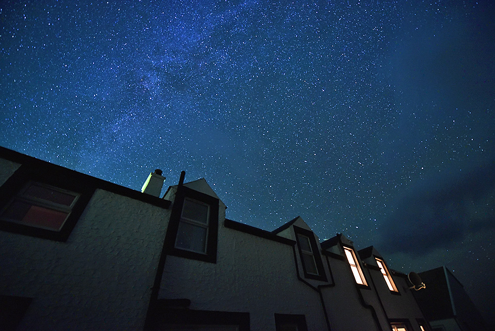 Picture of a starry night sky over a row of cottages