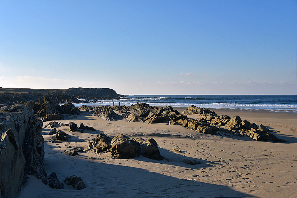 Picture of a bay with rocks and a sandy beach at low tide