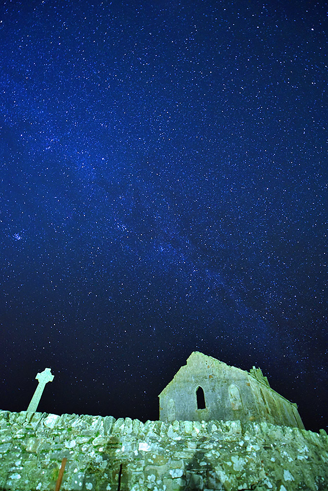 Picture of a starry night sky (with the Milky Way) over a Celtic cross and the ruin of a church