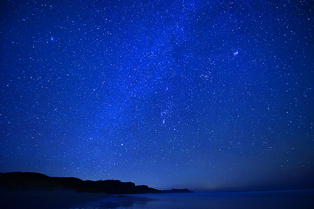 Picture of a sky filled with stars over a bay with a sandy beach