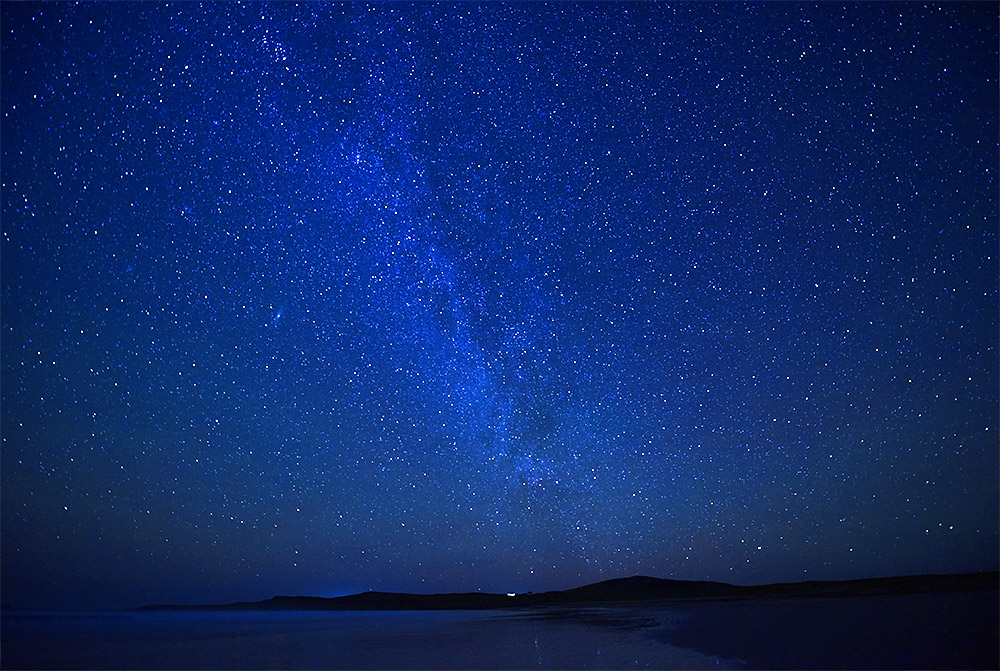 Picture of a star studded night sky over a bay with a beach