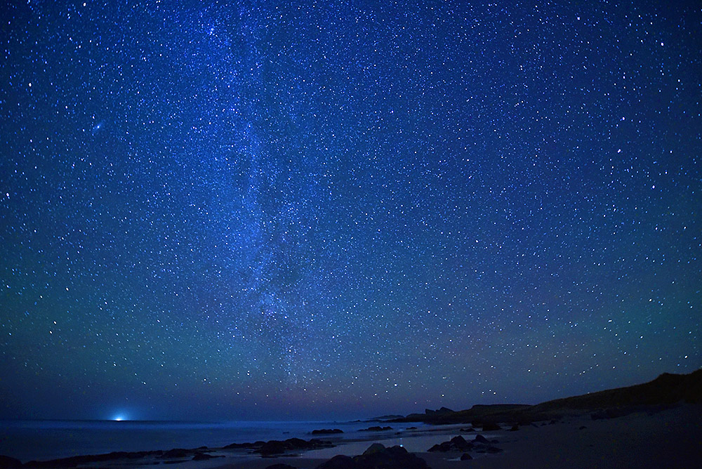 Picture of a night sky with thousands of stars over a coastline with beach, dunes and cliffs