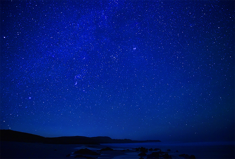 Picture of a night sky full of stars over a bay with a beach