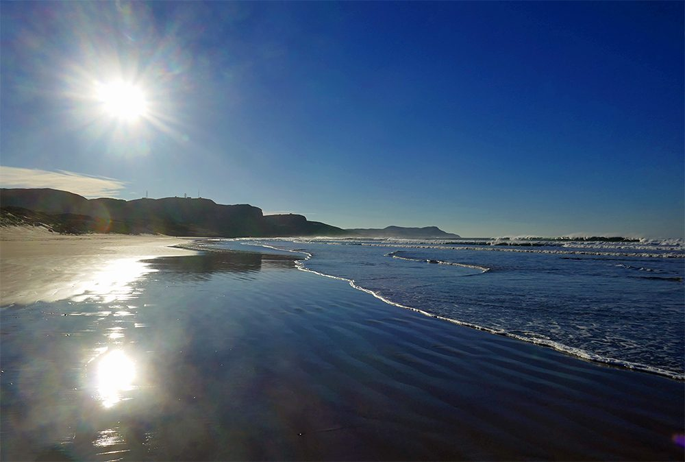 Picture of a wet beach with waves rolling in on a bright and sunny November morning