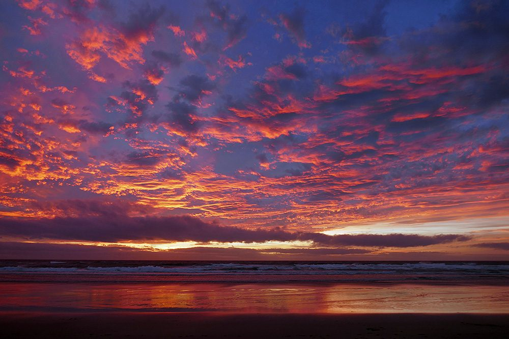Picture of colourful red, orange and yellow clouds over a bay at sunset
