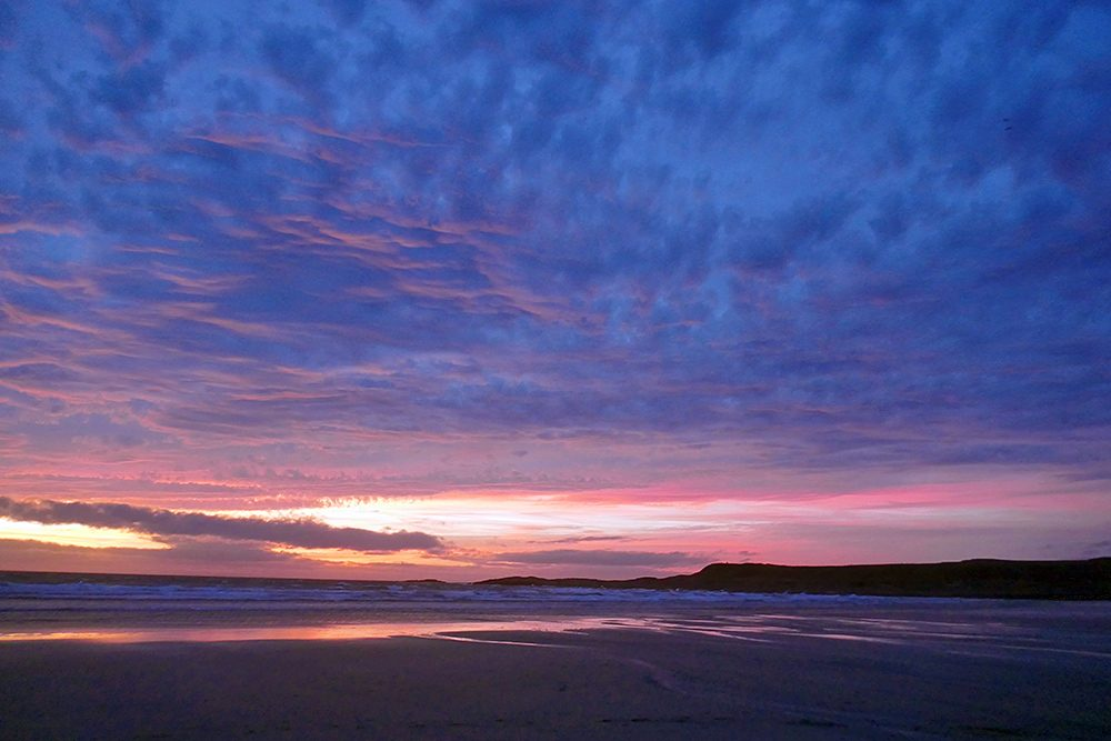 Picture of a colourful cloudy sky with the colours fading away over the northern end of a bay with a beach