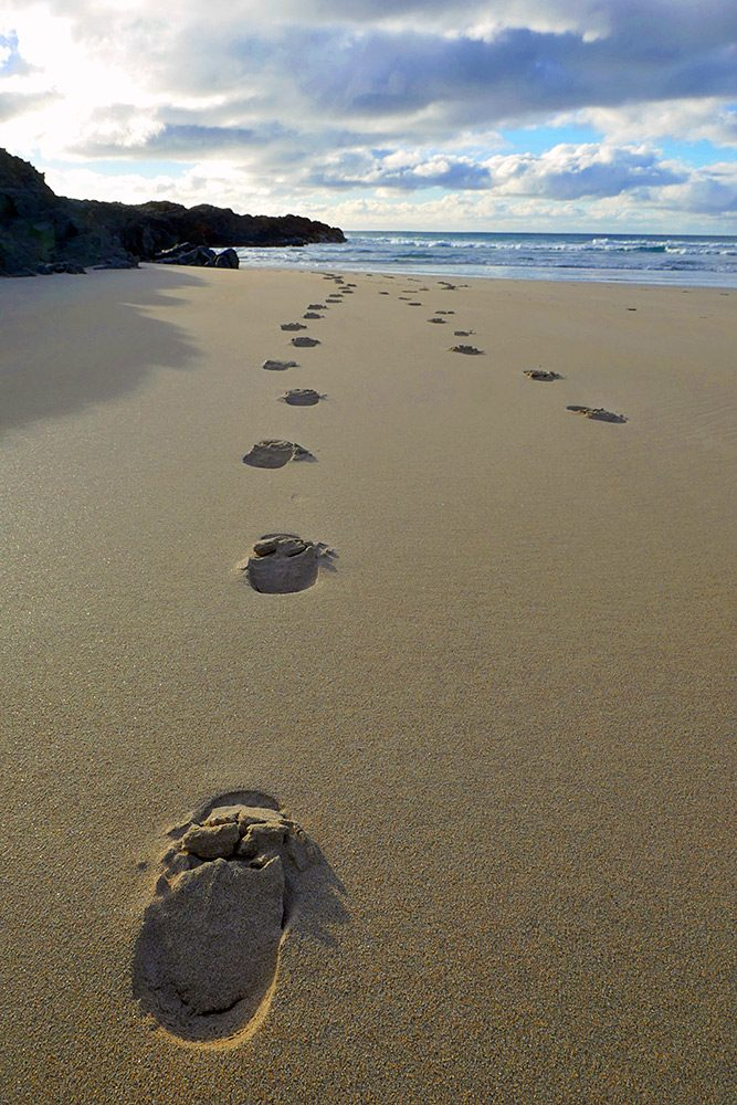 Picture of footprints on a beach next to rocks at the end of the beach