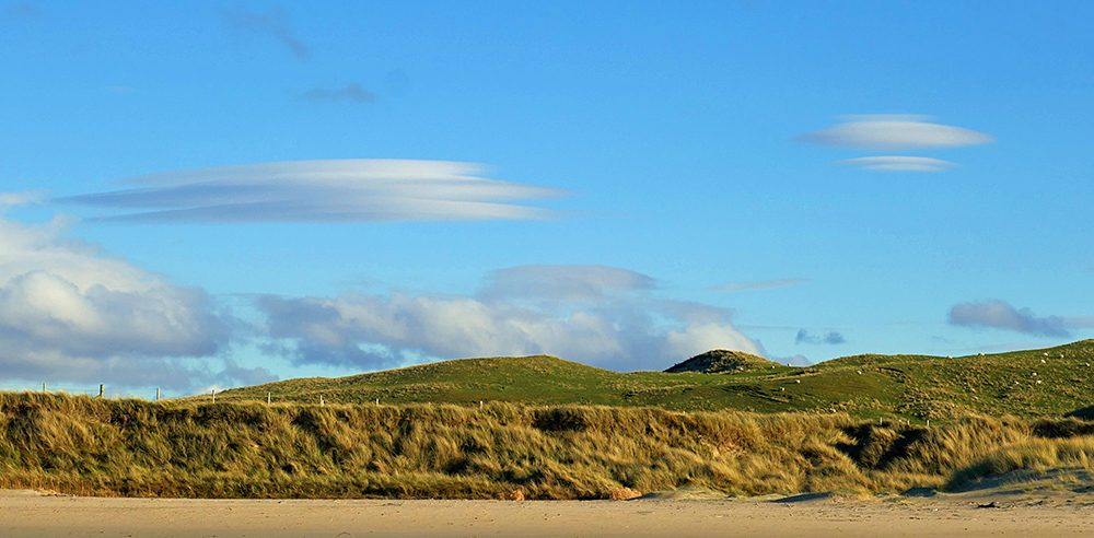 Picture of two lenticular clouds over some dunes behind a beach