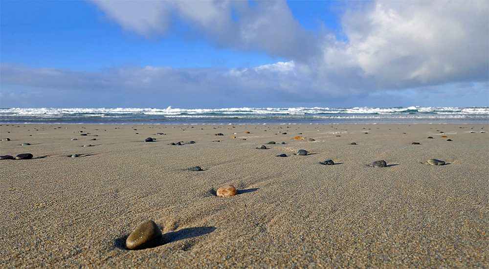 Picture of pebbles on a sandy beach, waves rolling in the background