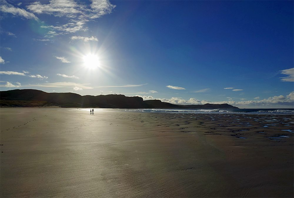 Picture of two walkers in the distance on a sandy beach with the bright Sun right above