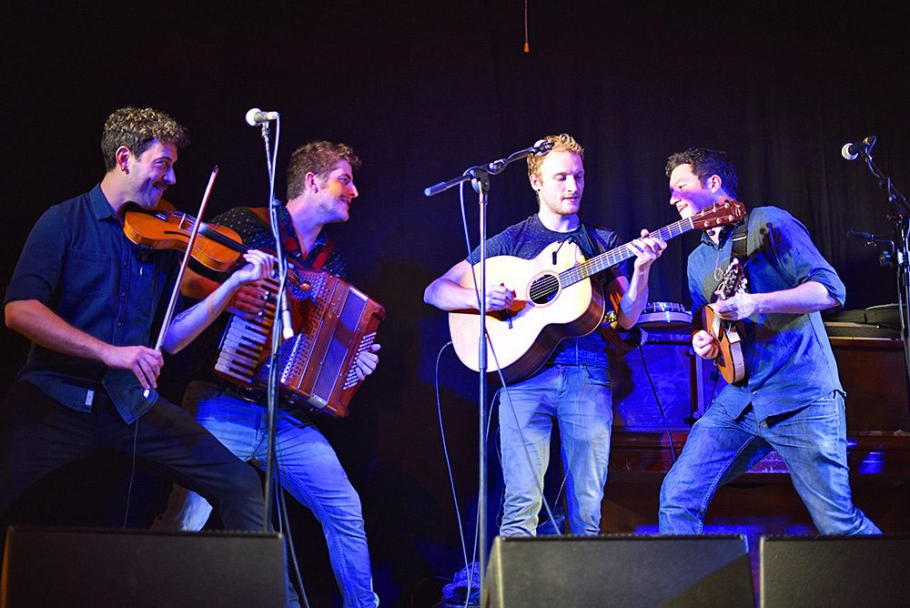 Picture of four members of the folk band Dallahan on stage