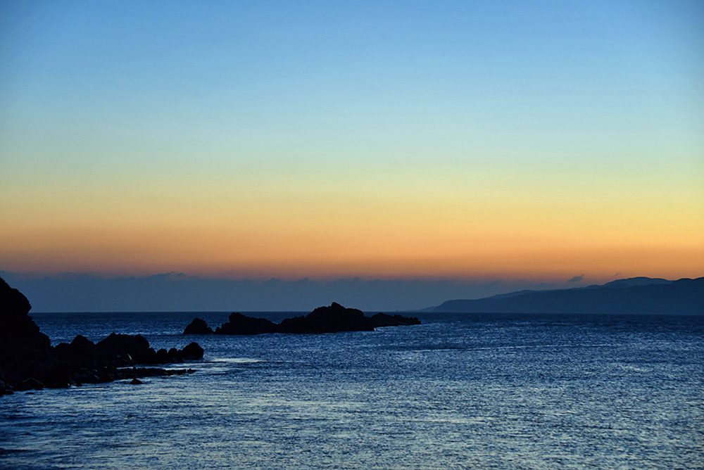 Picture of the gloaming just after sunset on a coast with rocks