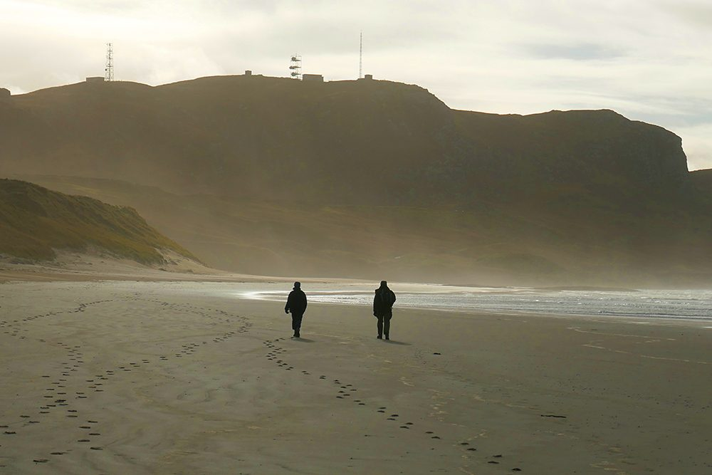 Picture of two walkers on a beach below some steep crags