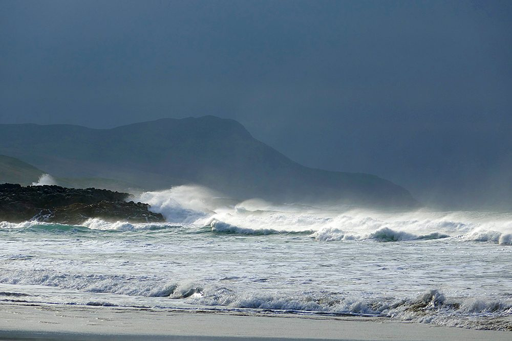 Picture of a bay on dark moody day, waves breaking and spray blown in the air