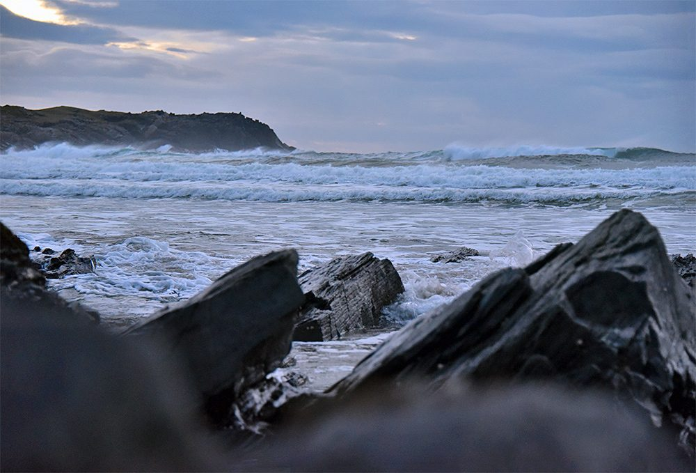 Picture of waves rolling into a bay seen through coastal rocks