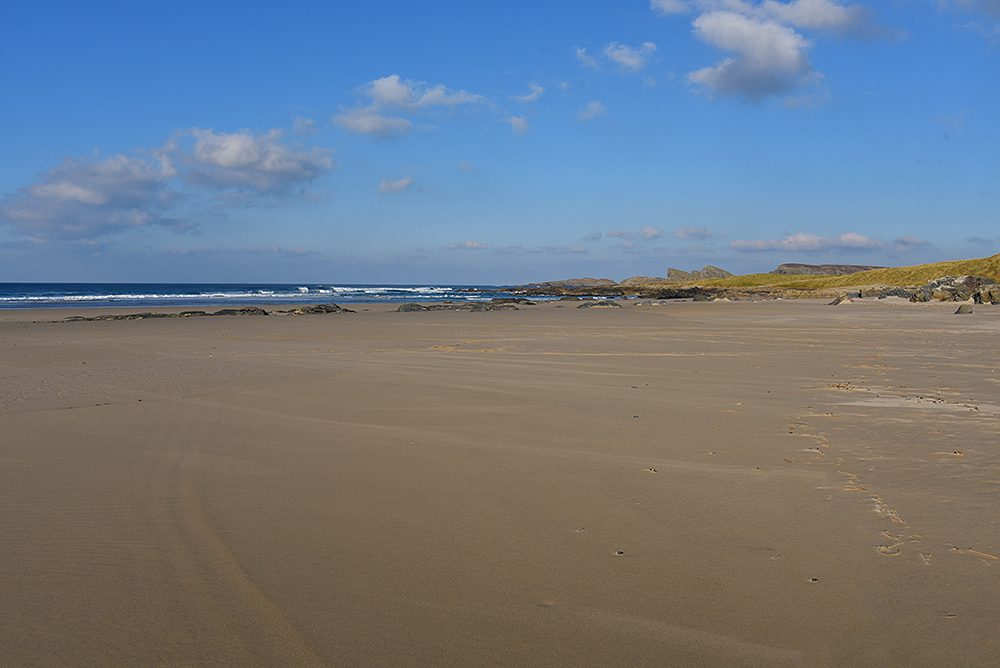 Picture of a wide sandy beach at low tide in the November sun