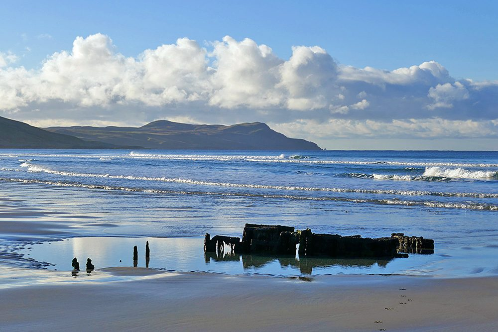 Picture of a wreck mostly hidden in the sand of a beach on a bright November morning