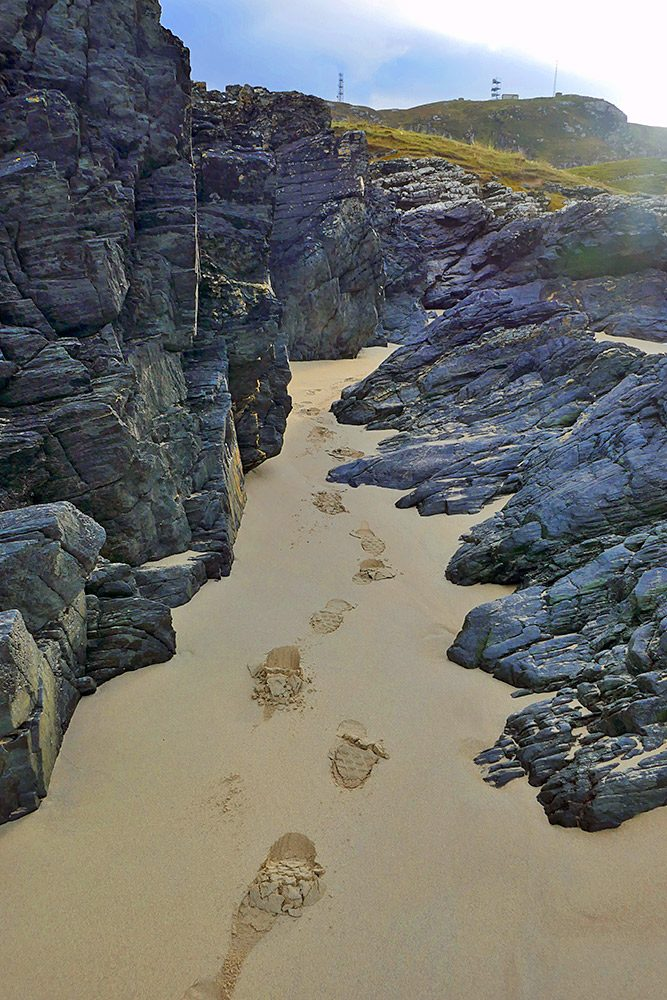 Picture of footprints in a narrow stretch of sand between some rocks