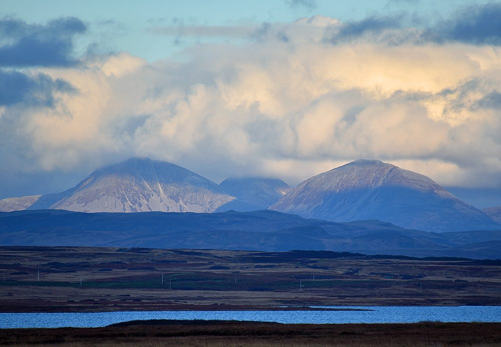 Picture of three mountains partially in the light and partially in the shade, seen across a loch (lake)