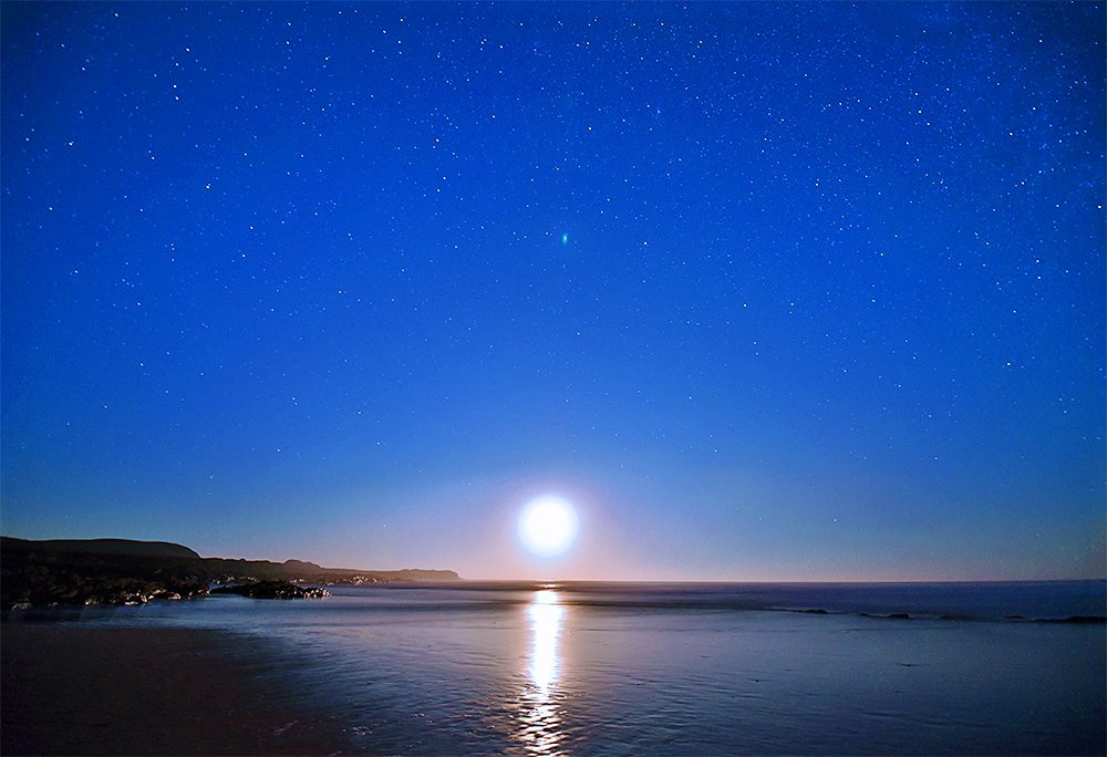 Picture of the Moon setting over a bay on a clear November night with lots of stars in the sky