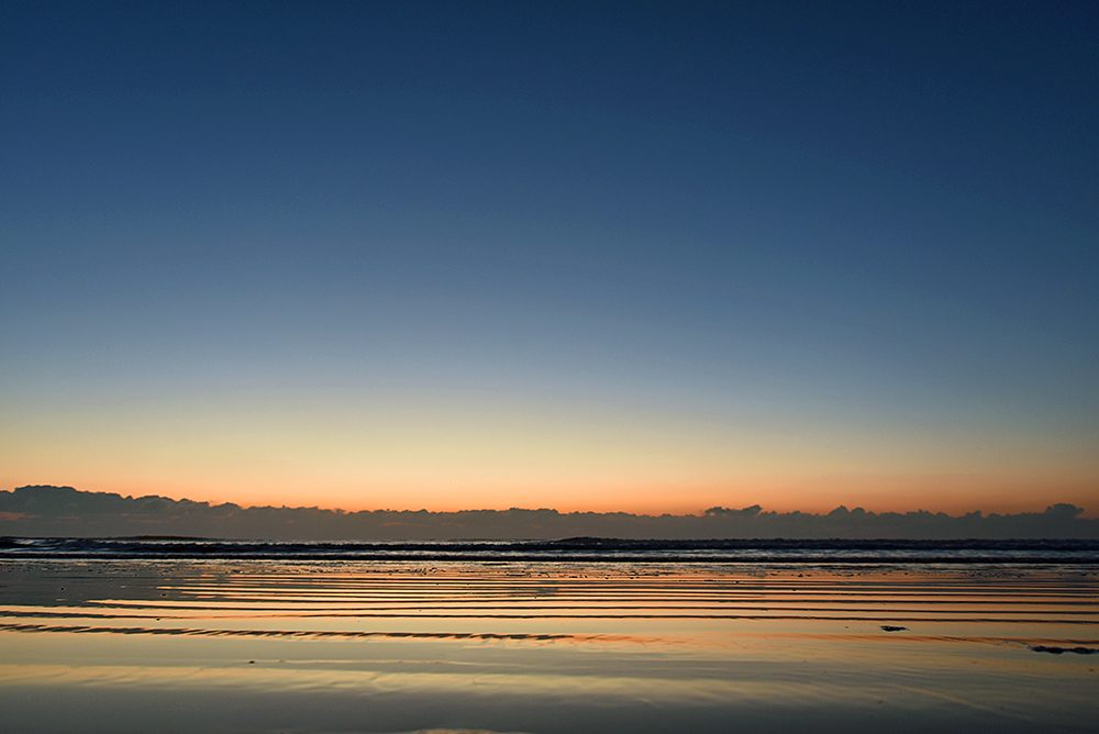 Picture of a beach under a clear sky during the gloaming, some clouds on the horizon