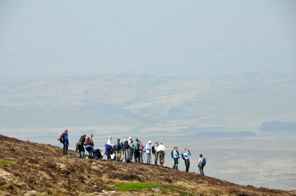 Picture of a group of walkers on the crest of a hill, more hills hiding in the haze in the background