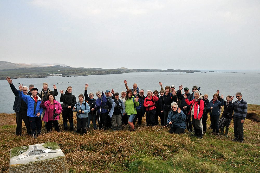 Picture of a group of walkers near a trig point on a small island, a larger island in the background