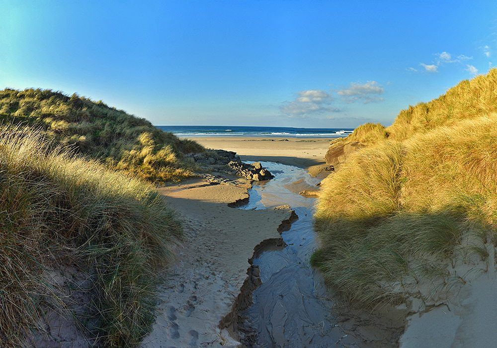 Panoramic picture of a view between dunes towards a beach, a small stream of water running through the dunes