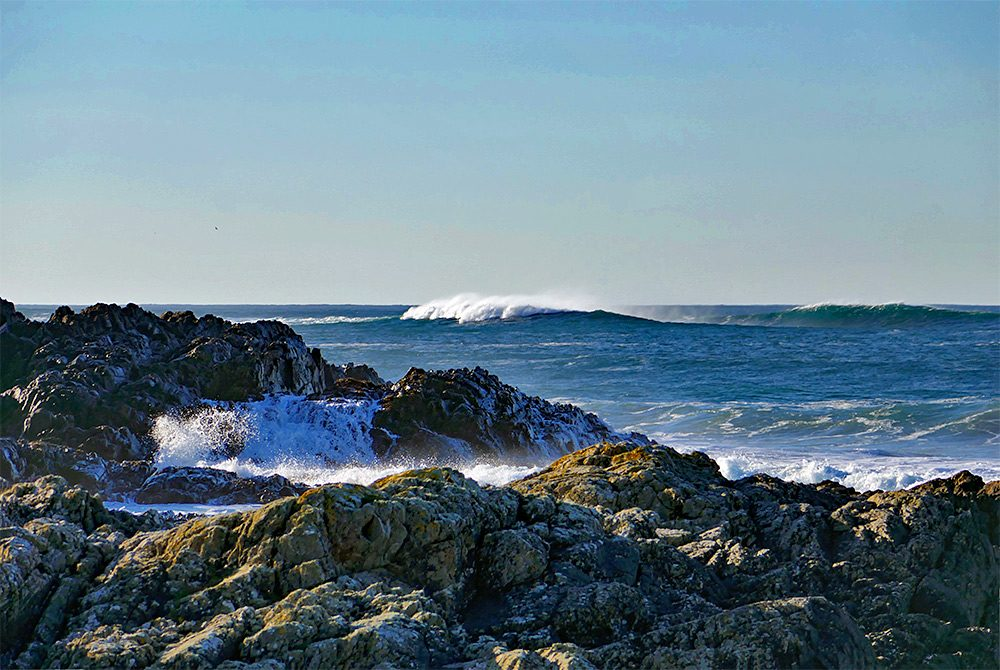 Picture of large rolling waves breaking just off a rocky shore