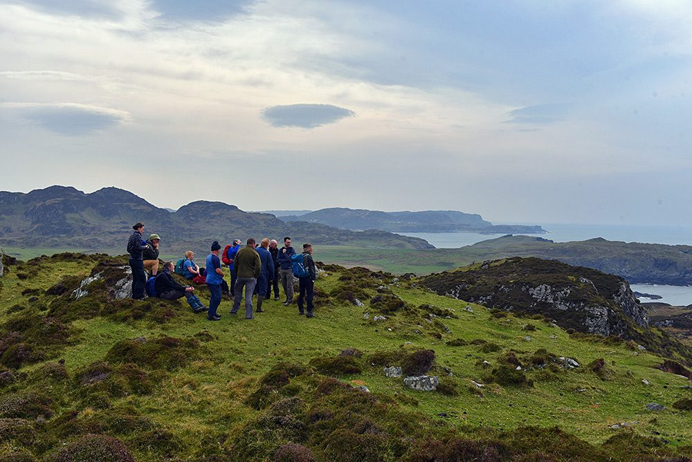 Picture of a group of walkers on top of a small hill on an island