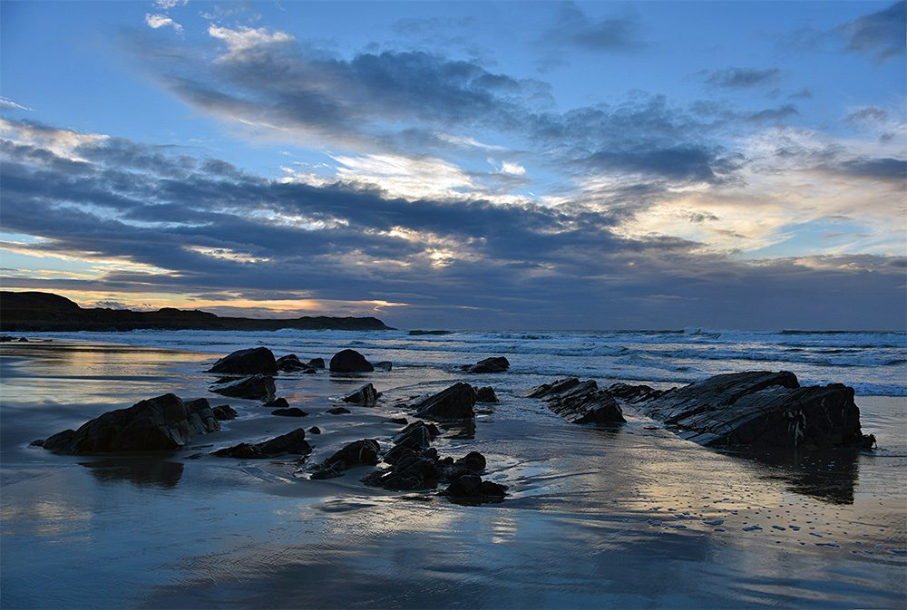 Picture of rocks in a sandy beach on a moody partly cloudy November afternoon