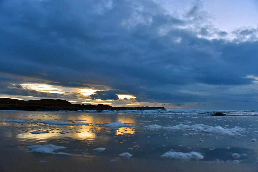 Picture of a dramatic sky reflecting in the wet sand of a beach in a bay