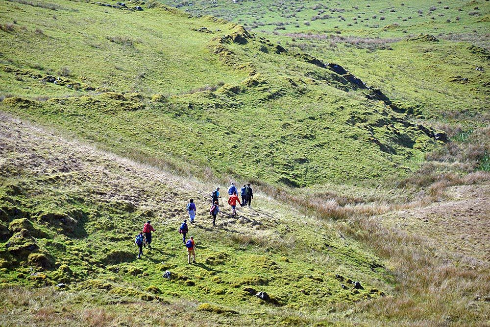 Picture of a group of walkers descending a hill, seen from the hill