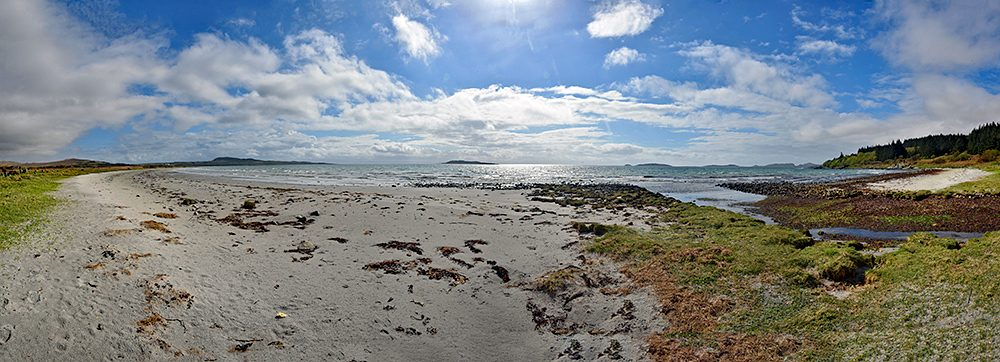 Panoramic picture of a wide bay with a sandy beach, some small islands in the distance