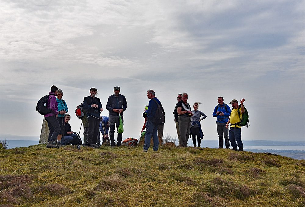 Picture of a group of walkers at the trig point on the top of a hill