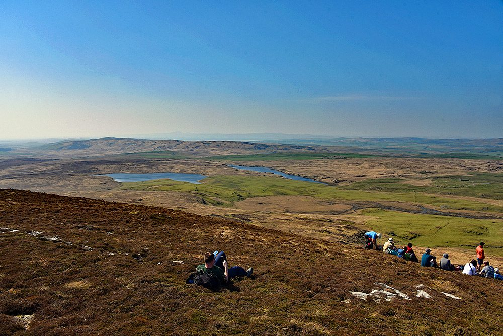 Picture of a group of walkers resting on the top of a hill for lunch