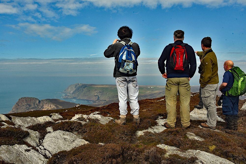 Picture of some walkers enjoying the view from a coastal hill over some steep cliffs