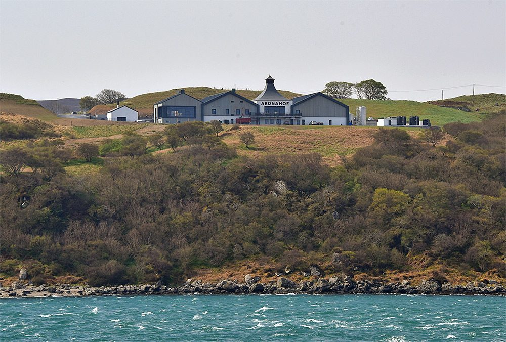 Picture of a new distillery on the hill side above a sound between two islands