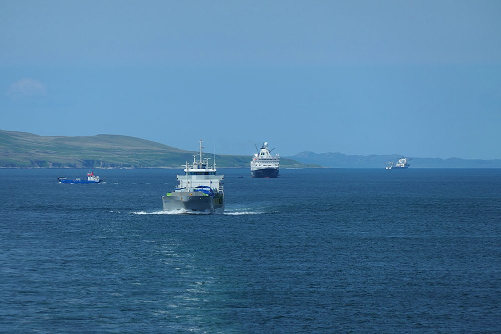Picture of a sound between two islands with five different ships/boats going about their business