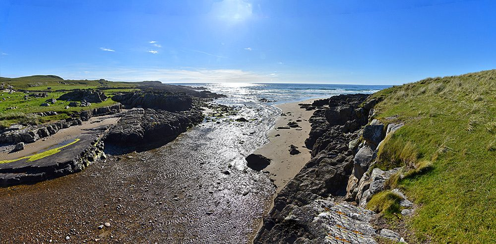 Panoramic picture of a small river flowing across a beach into the sea