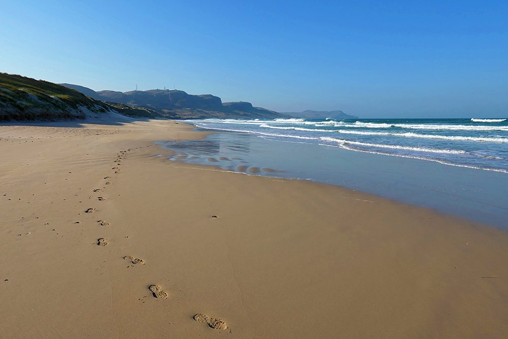 Picture of footprints on a beach on a bright sunny day