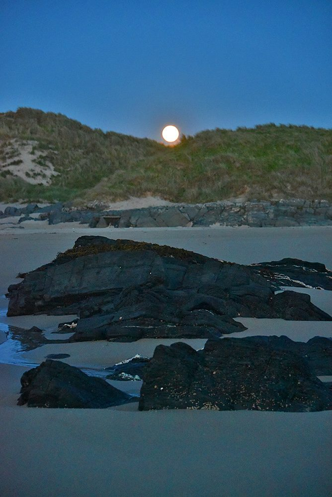 Picture of a bright full Moon rising above a small gap in dunes behind a beach