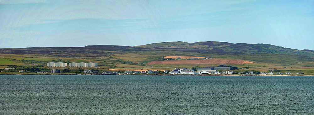 Panoramic picture of a coastal village with a distillery and the distillery warehouses