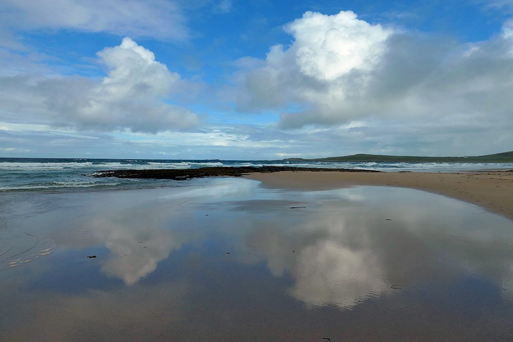 Picture of dramatic clouds reflecting on a wet beach
