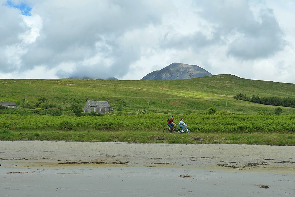 Picture of a couple cycling on a path next to a beach, hills and mountains in the background
