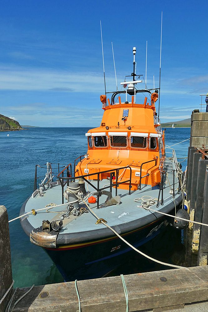Picture of a RNLI lifeboat at a pier in a sound between two islands