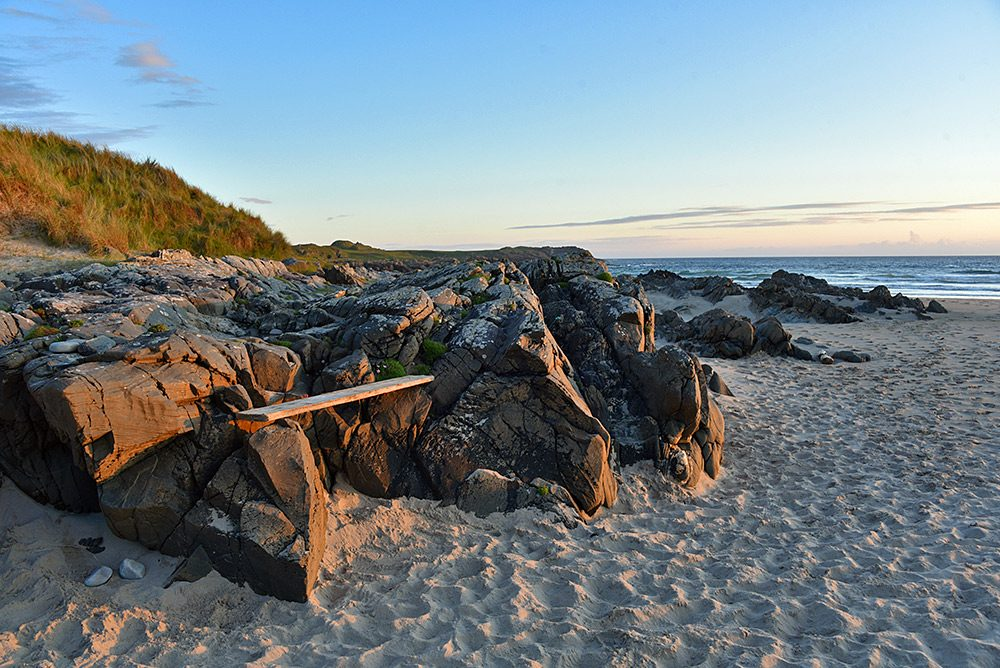 Picture of a wooden plank on some rocks creating a bench, illuminated by the June evening sun