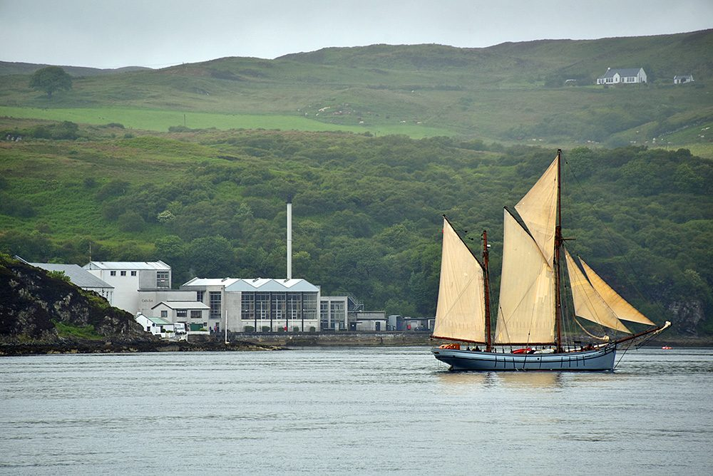 Picture of an old sailing ketch passing a modern distillery